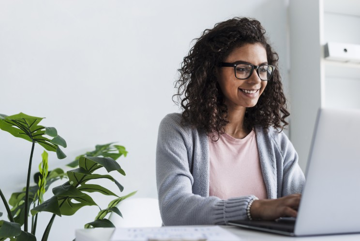 A smiling young woman sitting at her computer, happy she's making a difference to coronavirus-impacted communities by donating through workplace giving.