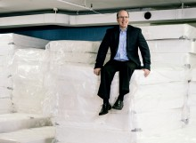Man sitting on large stacks of mattresses