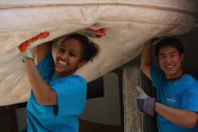 Two volunteers carry a mattress