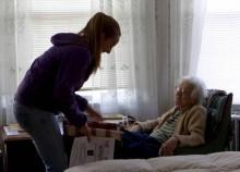 Woman serves elderly woman Meals on Wheels